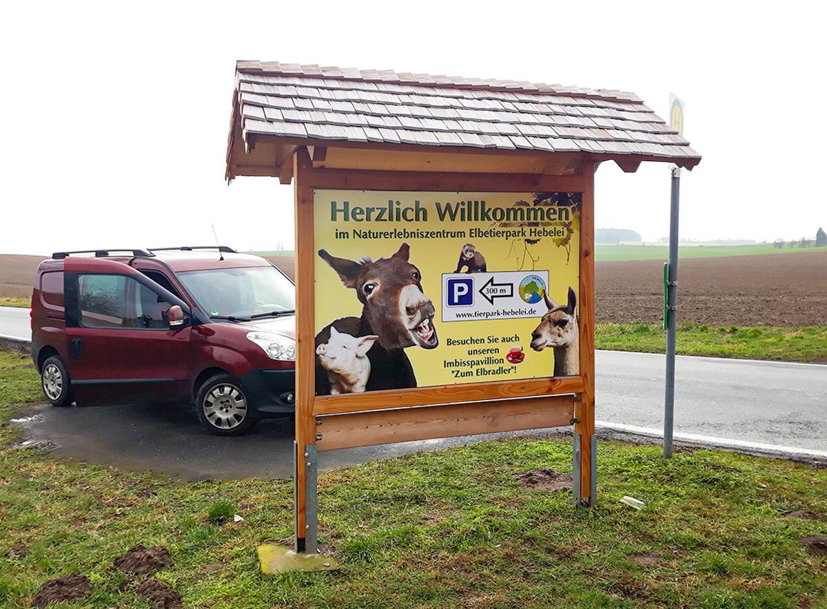 Beschilderung Tierpark Hebelei, Infotafel und Auto an der Straße
