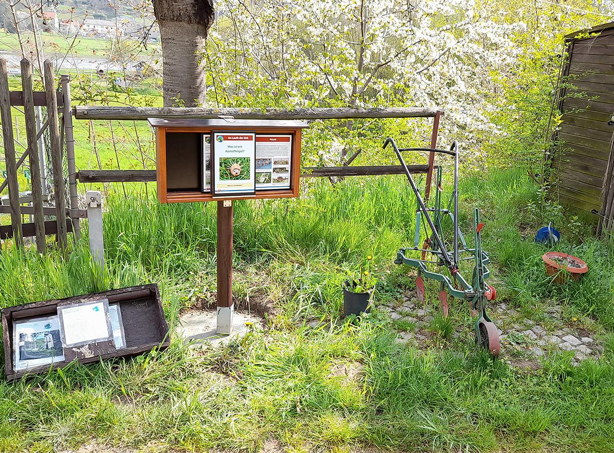 Beschilderung Tierpark Hebelei, Kasten mit Schild, daneben Baum und landwirtschaftliches Gerät